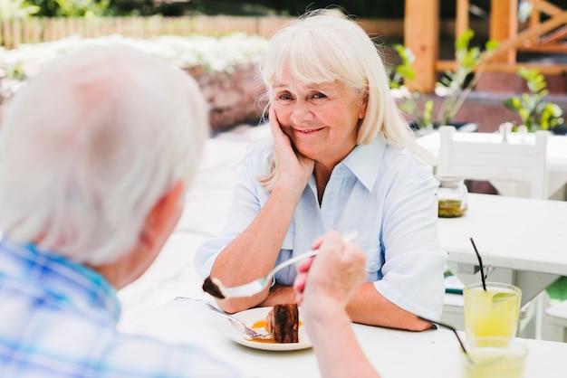 Bejaarde met echtgenoot die cake op buitenveranda eet