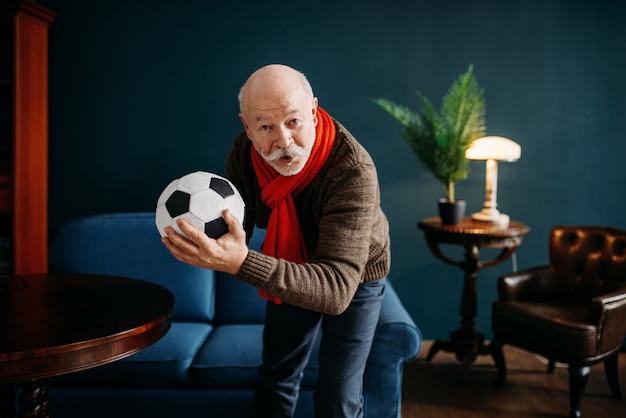 Bejaarde met rode sjaal en bal, voetbalfan