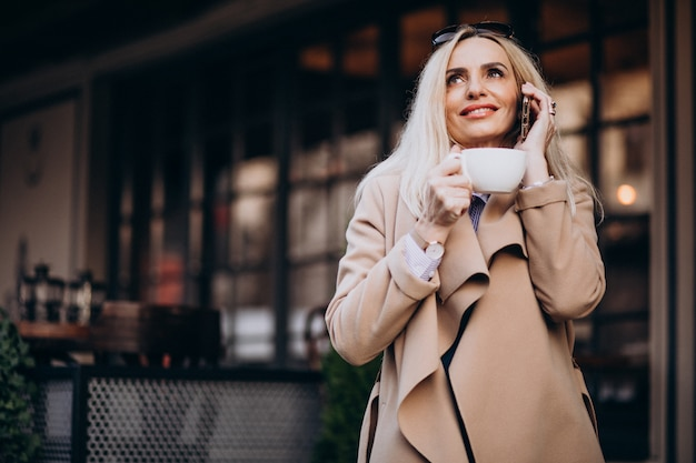 Bejaarde onderneemster die koffie buiten koffie drinken en op de telefoon spreken
