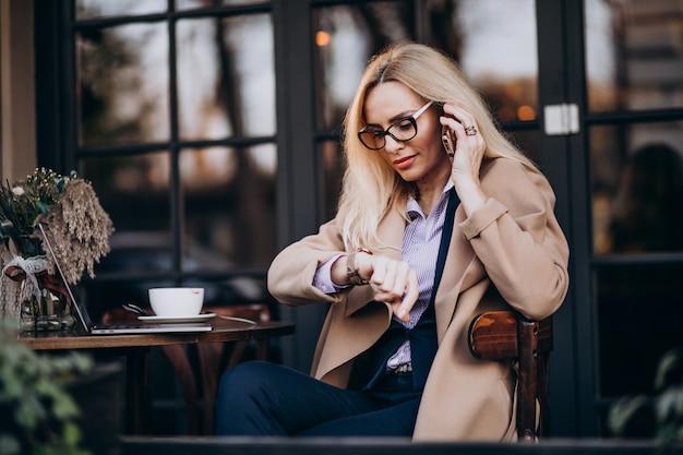 Bejaarde onderneemster die op telefoon spreekt en buiten het koffie zit