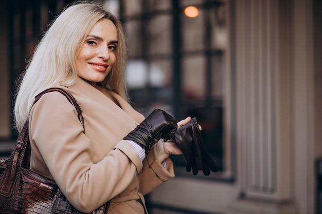 Bejaarde onderneemster in een jas die handschoenen in de straat draagt