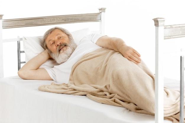 Bejaarde oude mens die in een geïsoleerd het ziekenhuisbed terugkrijgt