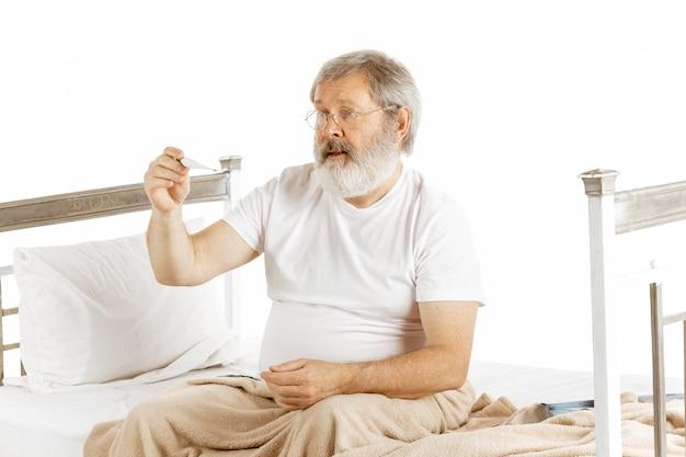 Bejaarde oude mens die in een het ziekenhuisbed terugkrijgen dat op wit wordt geïsoleerd