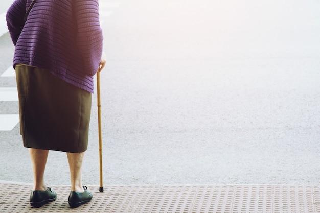 Bejaarde oude vrouw met wandelstok staan te wachten op voetpad stoep