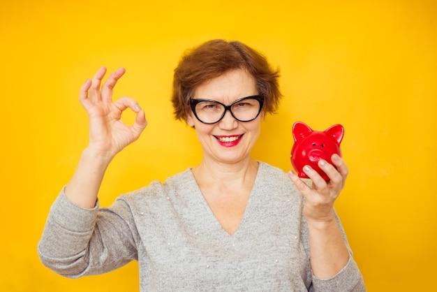 Bejaarde positieve vrouw met spaarvarken op gele achtergrond