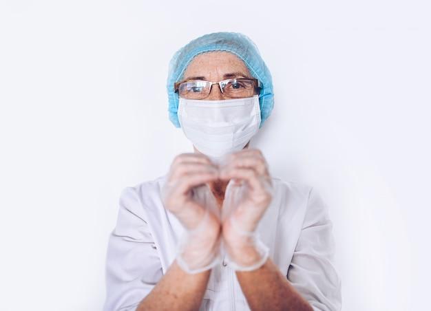 Bejaarde rijpe vrouwenarts of verpleegster die hartteken in een witte medische laag, handschoenen, gezichtsmasker dragen die persoonlijk geïsoleerd beschermingsmiddel dragen. gezondheidszorg en geneeskunde concept. covid-19-pandemie