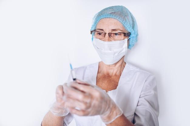 Bejaarde rijpe vrouwenarts of verpleegster met spuit in een witte medische laag, handschoenen, gezichtsmasker dat geïsoleerd persoonlijk beschermingsmiddel draagt. gezondheidszorg en geneeskunde concept. covid-19 pandemische crisis