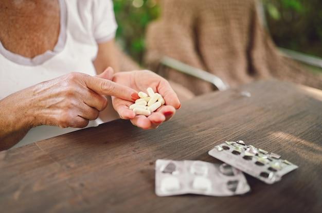 Bejaarde senior oude vrouw handen met medicijnen drugs vitaminen pillen buiten in de tuin. gezondheidszorg ouderen levensstijl concept
