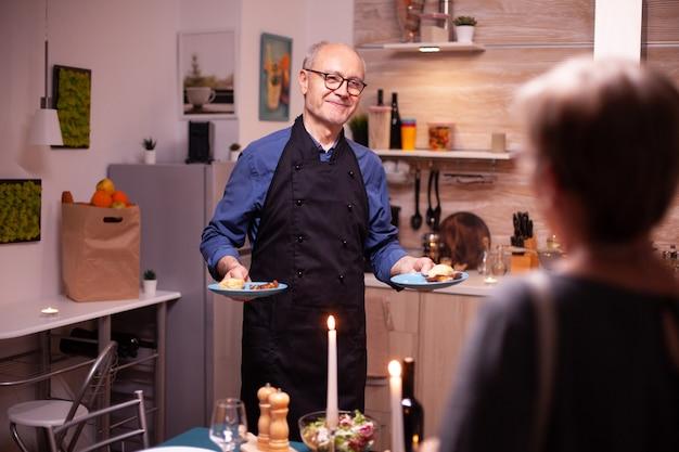 Bejaarde senior serveert diner aan zijn vrouw tijdens een romantisch diner. senior koppel praten, aan de tafel in de keuken zitten, genieten van de maaltijd, hun jubileum vieren in de eetkamer.