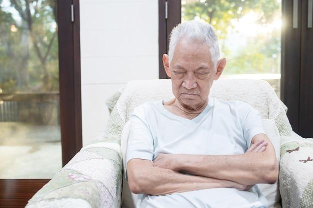Bejaarde slaapt op zijn bank