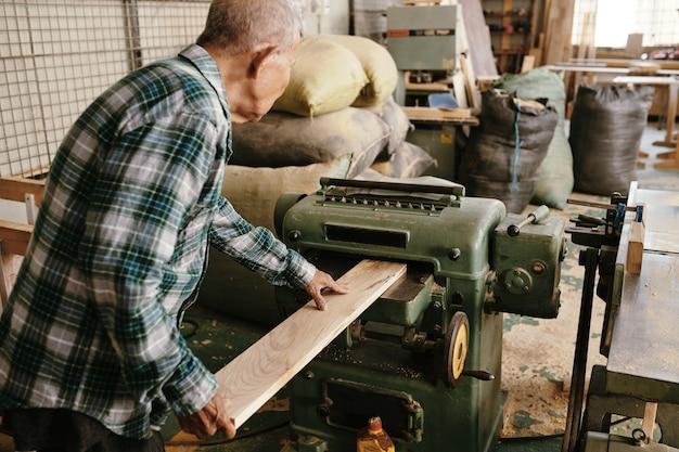Bejaarde timmerman in geruit hemd met behulp van dikteschaafbord tot consistente dikte over de hele lengte en plat op beide oppervlakken