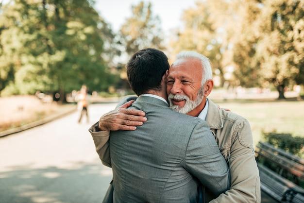 Bejaarde vader en volwassen zoon die in het park koesteren.