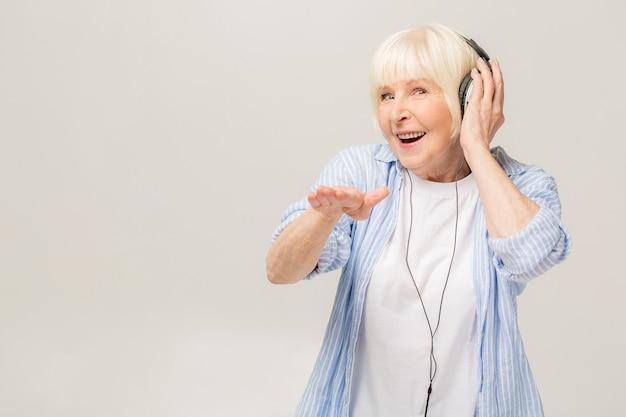 Bejaarde vrolijke vrouw met koptelefoon luisteren naar muziek op een telefoon geïsoleerd op een witte achtergrond.