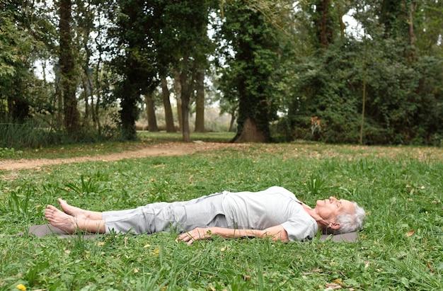Bejaarde vrouw beoefenen van yoga buitenshuis