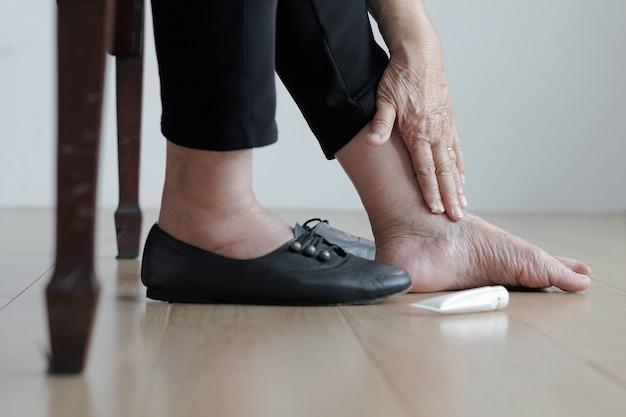 Bejaarde vrouw crème op gezwollen voeten zetten voordat schoenen aantrekken