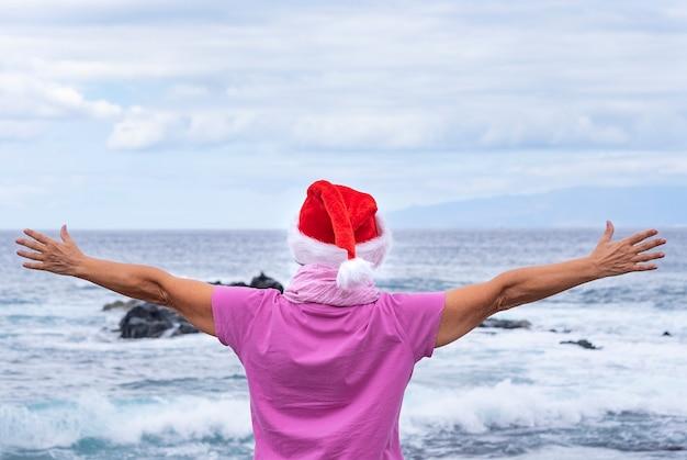 Bejaarde vrouw die een beschermend masker draagt dat op het strand staat met open armen en een kerstmuts draagt