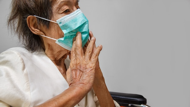 Bejaarde vrouw die een masker draagt om te beschermen tegen coronavirus covid-19
