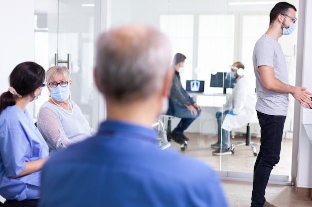 Bejaarde vrouw die gezichtsmasker draagt als veiligheidsmaatregel tegen coronavirus tijdens wereldwijde pandemie met coronavirus in de wachtkamer van het ziekenhuis