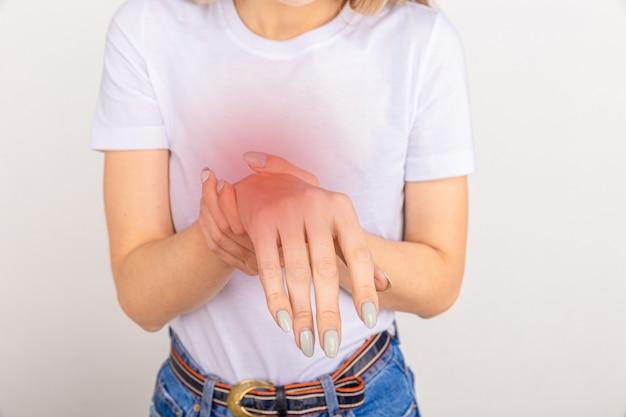 Bejaarde vrouw die lijdt aan pijn, zwakte en tintelingen in de pols. oorzaken van pijn zijn artrose, reumatoïde artritis, jicht of polsverstuiking. gezondheidszorg concept