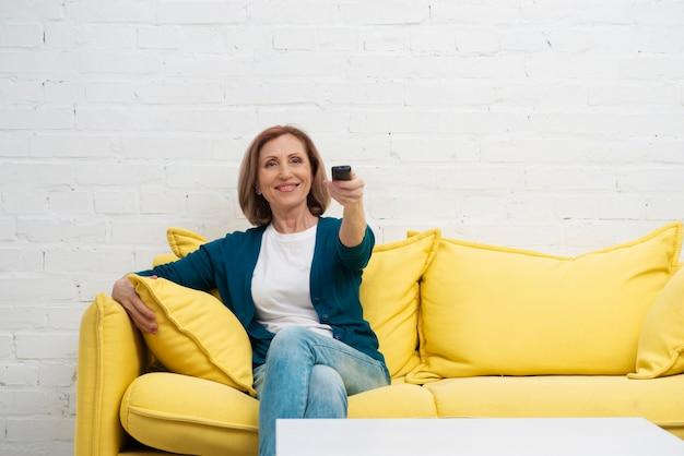 Bejaarde vrouw die televisiekanalen verandert Gratis Foto