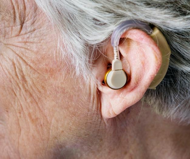 Bejaarde vrouw draagt een gehoorapparaat