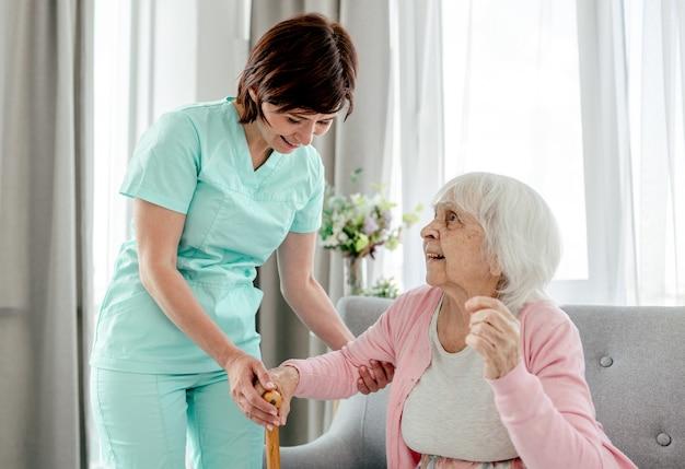 Bejaarde vrouw en verpleegster thuis. meisje in de gezondheidszorg geeft om senior vrouwelijke persoon binnenshuis