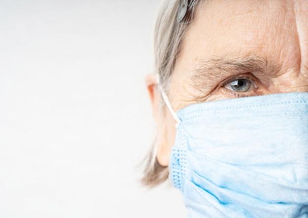 Bejaarde vrouw gerimpeld gezicht in beschermend medisch masker
