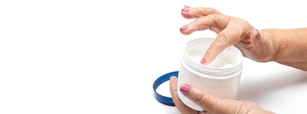 Bejaarde vrouw haar handen afroming close-up. cosmetische hydraterende verzorging voor de oude huid. handverzorging en behandeling tegen veroudering. zalf voor de behandeling van gewrichten bij ouderen.