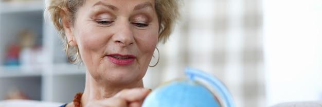 Bejaarde vrouw houdt blauwe wereldbol in haar hand en wijst met haar wijsvinger naar continent