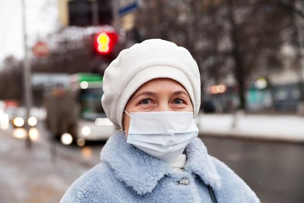Bejaarde vrouw in de winterkleren en medisch masker op straat. het thema bescherming tijdens een uitbraak van coronavirus