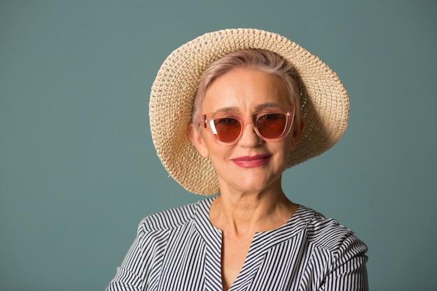 Bejaarde vrouw in een hoed op een blauwe achtergrond