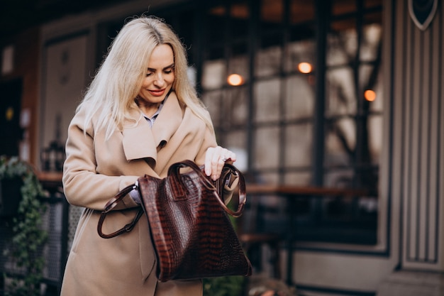 Bejaarde vrouw in een jas buiten het café