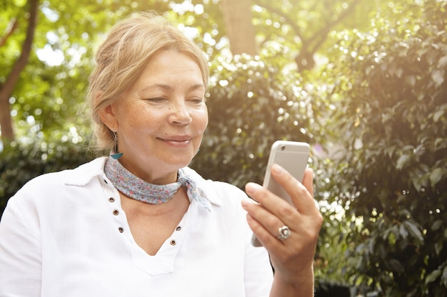 Bejaarde vrouw in park met behulp van telefoon