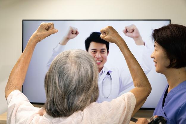 Bejaarde vrouw met behulp van fysiotherapie online service thuis.