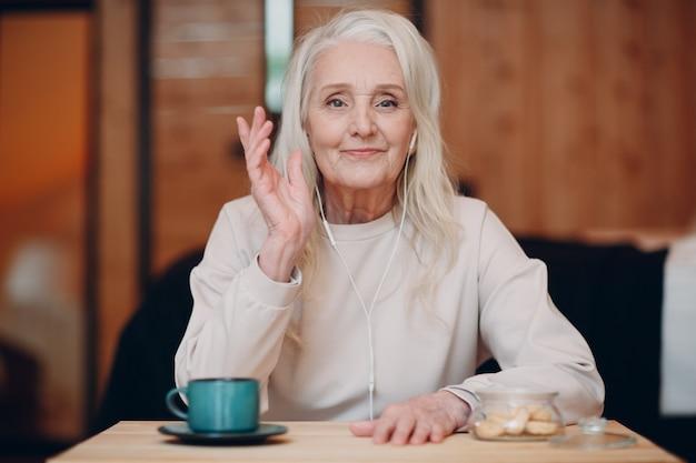 Bejaarde vrouw met koptelefoon praten video-oproep op laptop in de keuken, zwaaien op scherm, chatten en spreken.