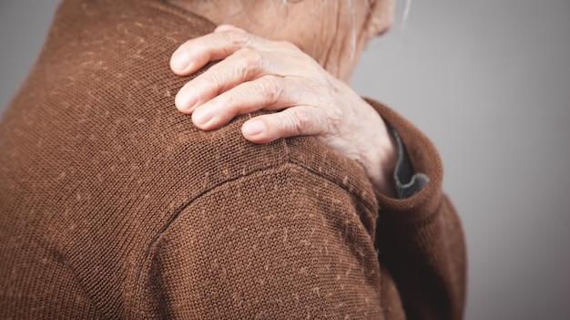 Bejaarde vrouw met pijn in de schouder.
