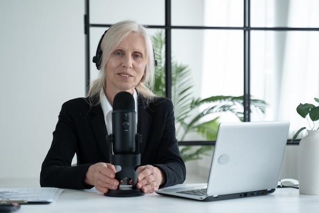 Bejaarde vrouw neemt een podcast op haar laptop op met koptelefoon en microfoon