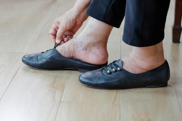 Bejaarde vrouw schoenen aantrekken.