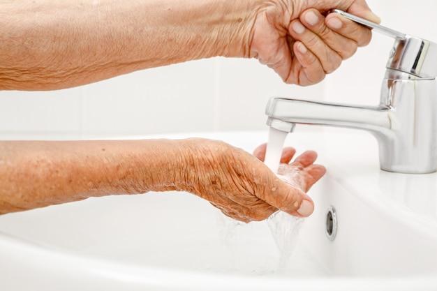Bejaarde vrouw wast hand in badkamer