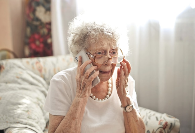 Bejaarde vrouw zittend aan een telefoongesprek met een bezorgde blik op haar gezicht