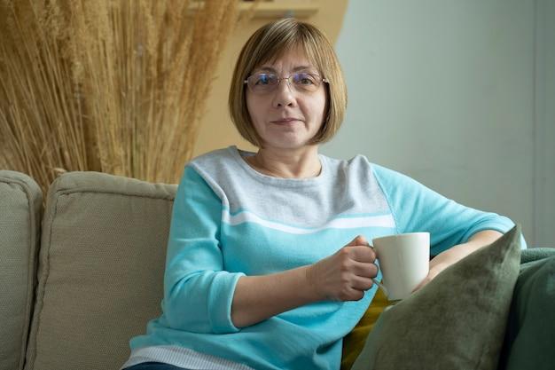 Bejaarde vrouw zittend op de bank in haar woonkamer en met een kopje koffie terwijl ze lacht naar de camera