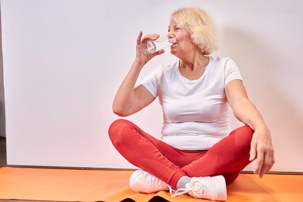 Bejaarde vrouw zoet water drinken na sportoefeningen op de vloer, rust. gezonde levensstijl concept