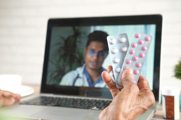 Bejaarde vrouwen houden blisterverpakking tijdens overleg met arts op laptop