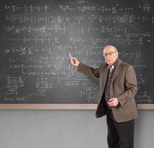 Bejaarde wiskundeleraar in de buurt van een schoolbord
