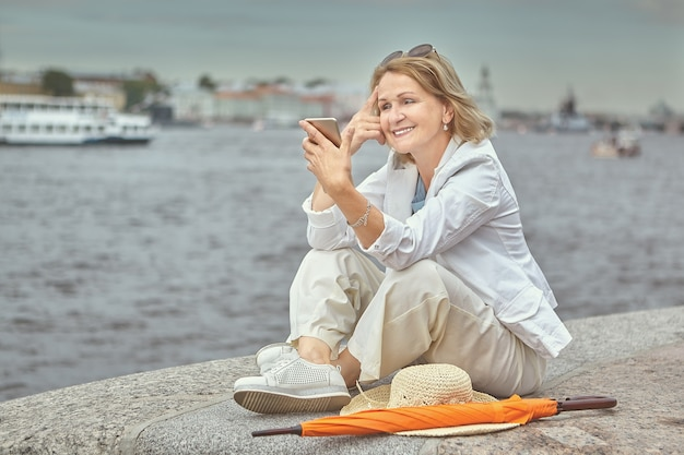 Bejaarde witte vrij lachende dame 62 jaar oud zit bij de rivier tijdens een wandeling in de binnenstad met mobiele telefoon in handen.