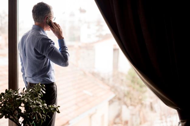 Bejaarde zakenman die door venster kijkt terwijl gesprekken telefonisch