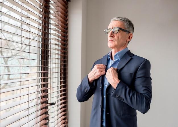 Bejaarde zakenman die door venster kijkt