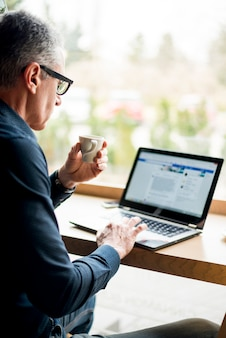 Bejaarde zakenman die in laptop werkt