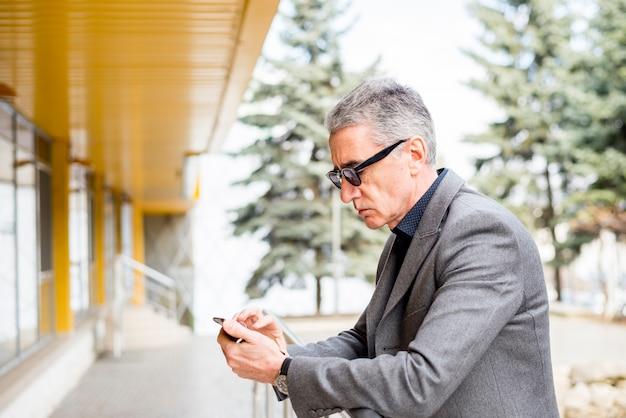 Bejaarde zakenman die mobiele telefoon in openlucht met behulp van
