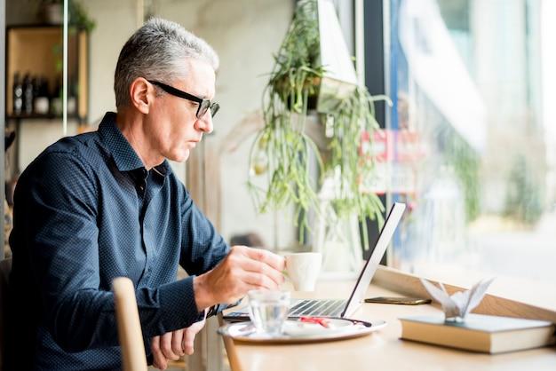 Bejaarde zakenman die terwijl het hebben van koffie werkt